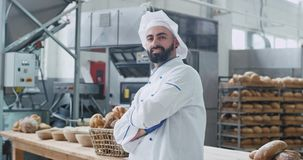 Panadero atractivo del hombre en una sonrisa elegante del uniforme grande delante de la cámara él que disfruta del tiempo en su l almacen de metraje de vídeo