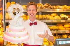 Panadero con el pastel de bodas en confitería fotos de archivo libres de regalías