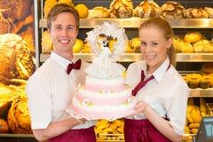 Panadero con el pastel de bodas en confitería foto de archivo