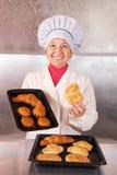 Panadero con los pasteles frescos foto de archivo