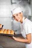 Panadero de sexo femenino feliz With Fresh Breads en bandeja de la hornada Imágenes de archivo libres de regalías