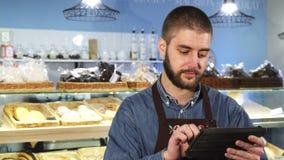 Panadero de sexo masculino profesional hermoso que usa la tableta digital en su tienda metrajes