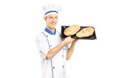 Panadero de sexo masculino sonriente que sostiene los panes recientemente cocidos Fotos de archivo libres de regalías