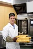 Panadero feliz que muestra sus baguettes en su panadería Imágenes de archivo libres de regalías