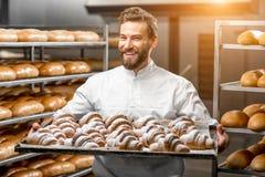Panadero hermoso que sostiene la bandeja llena de croisants recientemente cocidos foto de archivo