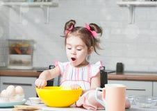 Panadero lindo de la niña en cocina con los ingredientes de la hornada foto de archivo libre de regalías