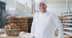 Panadero maduro apuesto del hombre en una sonrisa grande del sector panadero grande y mostrar un gusto grande delante de la cámar almacen de metraje de vídeo