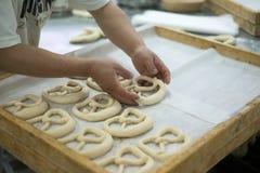 Panadero Placing Mirrored Pretzel en la bandeja Fotos de archivo