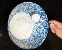 Panadero que añade la sal a la mezcla del pan Imágenes de archivo libres de regalías