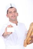 Panadero que muestra la tarjeta Fotografía de archivo libre de regalías