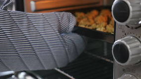 Panadero que pone las galletas en el horno almacen de metraje de vídeo