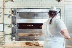 Panadero que sale el pan fresco con la pala del horno Fotografía de archivo libre de regalías