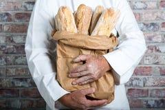 Panadero que sostiene los baguettes tradicionales del francés del pan Imagen de archivo