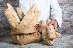 Panadero que sostiene los baguettes tradicionales del francés del pan Fotografía de archivo