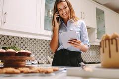 Panadero que toma órdenes en el teléfono imágenes de archivo libres de regalías