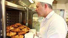 Panadero sonriente que saca los cruasanes frescos del horno metrajes