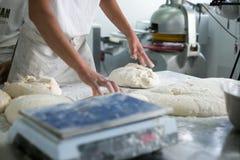 Panadero Tossing Flour en la pasta cruda Fotos de archivo