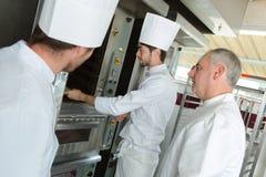 Panadero y ayudantes masculinos que usan el horno fotos de archivo