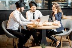 Panaderos con la empresaria en el café imagen de archivo
