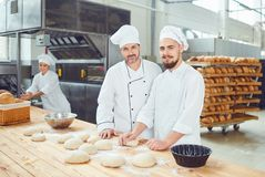Panaderos de los hombres en el lugar de trabajo en la panadería fotografía de archivo