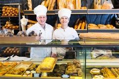 Panaderos maduros felices con pan fresco en panadería fotografía de archivo libre de regalías
