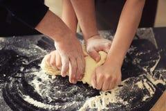 Panaderos que amasan la pasta en la tabla de cocina fotografía de archivo libre de regalías