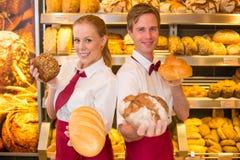 Panaderos que presentan los panes del pan en una panadería foto de archivo libre de regalías