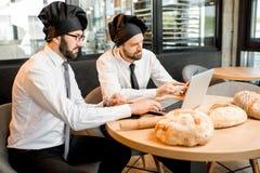 Panaderos que trabajan con pan en la oficina imágenes de archivo libres de regalías