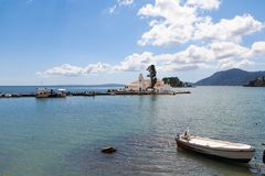 The Panagia Vlacherna Monastery of Panayia with a fisher boat. In the front in Corfu, Greece royalty free stock photo