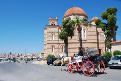 Panagitsa church, Aegina island. A horse and carriage giving rides to tourists passes the Panagitsa church on the harbour front of Aegina Town on the Greek Stock Photos