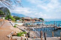 Panajachel Docks on the shore of Lake Atitlan in Guatemala. Old rickety wooden piers out into Lake Atitlan in Guatemala with the small village of Panajachel in Royalty Free Stock Photography
