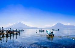 Panajachel Gwatemala, Kwiecień, -, 25, 2018: Łodzie przy molami w dalekiej wiosce San Pedro, jeziorny Atitlan w obraz royalty free