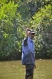 Panaji, Goa/Ινδία - 01/08/2012: Ινδικός ψαράς, ένα ηλικιωμένο άτομο ραβδιά στα παλαιά βαρκών από την ακτή Στοκ φωτογραφία με δικαίωμα ελεύθερης χρήσης