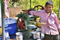 Panaji, Goa/la India - 01/08/2012: El muchacho indio prepara el jugo Imágenes de archivo libres de regalías