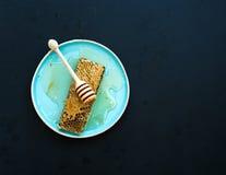 Panal con el cazo de la miel en la placa de cerámica azul Foto de archivo