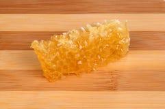 Panal con la miel en una tabla de cortar de madera Fotografía de archivo