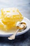 Panal con la miel que fluye en una placa y una cuchara Foto de archivo