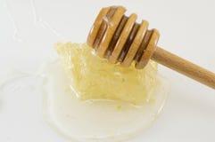 Panal con la miel y la cuchara del cazo en blanco Fotos de archivo