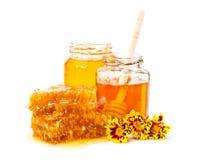 Panal dulce y dos tarros de miel con el palillo y las flores Foto de archivo