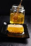 Panal en la placa y la miel en el tarro de cristal con la cuchara Imagen de archivo