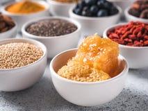 Panal en pequeño cuenco blanco y otros superfoods Imagen de archivo libre de regalías