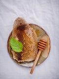 Panal en placa de cerámica con la hierbabuena y cazo en f blanca Imagenes de archivo
