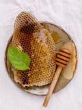 Panal en placa de cerámica con la hierbabuena y cazo en f blanca Foto de archivo libre de regalías