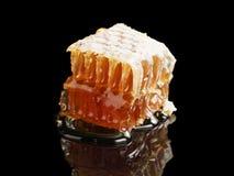 Panal orgánico con la miel aislada en fondo negro Foto de archivo libre de regalías