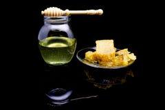 Panal orgánico con la miel aislada en fondo negro con la reflexión ciérrese para arriba de la cuchara natural del panal y de la m Foto de archivo libre de regalías