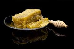 Panal orgánico con la miel aislada en fondo negro con la reflexión ciérrese para arriba de la cuchara natural del panal y de la m Fotos de archivo libres de regalías