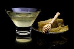 Panal orgánico con la miel aislada en fondo negro con la reflexión ciérrese para arriba de la cuchara natural del panal y de la m Foto de archivo