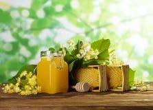 Panal y agitador, tarro con la miel en fondo verde claro Foto de archivo libre de regalías