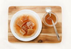 Panal y Honey Jar en el tablero de madera de la cocina, visión superior Imagenes de archivo