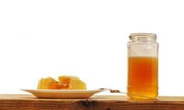 Panal y Honey Jar en la tabla de madera, en el fondo blanco Fotos de archivo